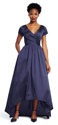 Luxurious yet simple, this stunning taffeta gown is ready to star at your next event. Featuring a high low hemline and adjustable bow in front, this long dress is ready for an evening out. This long formal gown has a v-neck bodice, short sleeves, and a hidden zip up back. Worn with metallic accessories, this dress makes elegance easy.