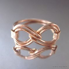 This gorgeous artisan made ring is made out of two parts. The top of the ring - the double infinity symbol if formed uniquely out of 18 gauge copper wire. The ring shank, hammer forged is made out of