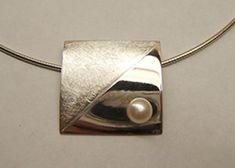 Rechthoekige, gebolde zilveren hanger met parel, de helft is diagonaal gematteerd