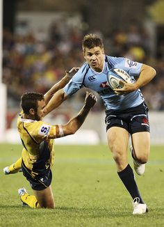 Drew Mitchell of the Waratahs fends off a tackle during the round four Super Rugby match between the Brumbies and the Waratahs at Canberra Stadium on March 9, 2013 in Canberra, Australia. #Rugby