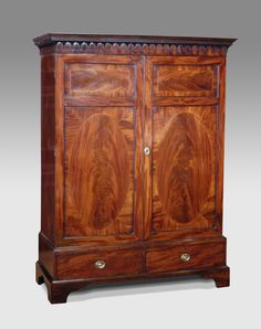 George III mahogany wardrobe. Dentil moulded cornice over an egg and dart frieze and two figured panel doors with inset flame veneered ovals and ebony and boxwood stringing. The interior lined and fitted with a hanging rail. The base section with two beaded drawers and raised on shaped bracket feet. alterations.  circa. 1800 £2400.00