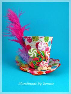 Dieses winzige Hut ist bedeckt mit Lollipop Spaß. Eine große rosa Feder Kaskaden von der Seite und vorgeben Candy macht dies zu einem wirklich Spaß und einzigartige Accessoire. Misst ca. 4 hoch, nicht einschließlich der Feder und 5 breit an der Basis. Ausgezeichnete Foto-Prop oder Ergänzung zu Ihrem Kostüm. Legen Sie dies auf ein Stirnband Ihrer Wahl (nicht im Lieferumfang enthalten) Meine Hüte sind von mir handgefertigt. Dies ist keine Mütze, die aus einer Fabrik gekauft wurde, die ich…