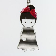 Sautoir poupée en plastique fou avec un chignon, une robe à rayures noires et un nœud rouge en ruban organdi. Par Naïas.