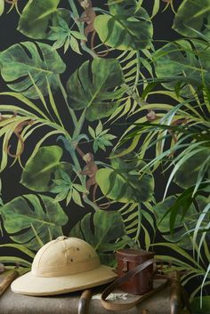 A fun green jungle leaf wallpaper design, set on a coloured background with mischievous monkeys leaping through the leaves.
