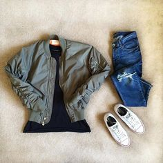 olive bomber. long black tee. medium wash blue jeans. white sneakers.