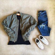 olive bomber. long black tee. medium wash blue jeans. white sneakers.