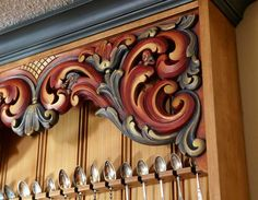 Troll-like caricatures peek around the scrollwork in the hand-carved Norwegian cabinet made by Hans Sandom.