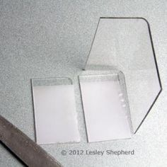 Round the top corners of the dollhouse display case using a file and sandpaper. - Photo © 2012 Lesley Shepherd