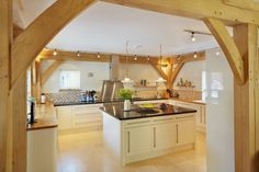 A picturesque, oak frame barn-style self-build home in Cambridgeshire. The new home features a timber clad exterior and a large area of south-facing glazing Barn Kitchen, Open Plan Kitchen, Kitchen Island, Kitchen Dining, Kitchen Cabinets, Flat Pack Homes, Oak Framed Extensions, Oak Framed Buildings, Oak Frame House