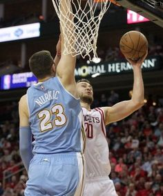 Rockets forward Donatas Motiejunas (20) shoots over Nuggets center Jusuf Nurkic (23) in the second half.
