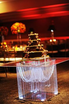 Forget the typical round table, and opt for a GORGEOUS acrylic table to sit your cake atop of! Add some lighting and crystal garlands (or other decor), and you have a GORGEOUS cake table! Cake Table Decorations, Balloon Decorations, Centerpieces, Wedding Decorations, Diy Wedding Bouquet, Bling Wedding, Wedding Cake Stands, Wedding Cakes, Battery Powered Led Lights