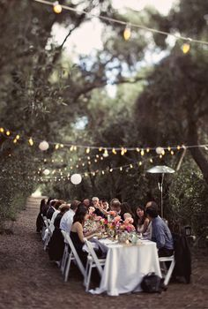 Cantina lighting, white tablecoths, bright flowers in an olive grove