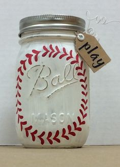 "Baseball Painted Mason Jar.  Used Folk Art Chalk paint, added details with small brush and F/A enamel paint, dried, sanded, sealed with spray acrylic sealer.  For detail work, used pencil to add a circle as a guide for stitching, 1 on each side of jar. Covered lid with burlap inside rim.  Used wire to attach a small tag that says ""play"".  Tag has eyelet, word added with stickers."