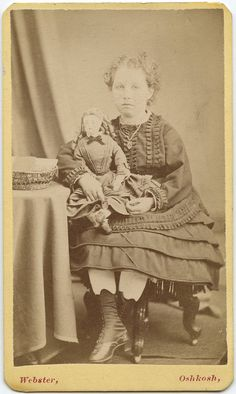 Vintage photo girl with her doll, circa 1875 - 1900.
