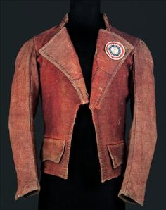 Carmagnole, 1790-1800. French. A carmagnole is a short woolen jacket worn by the working class. This jacket is not in very good shape because it was worn by working people that wore it out more than the wealthy royal would. On the collar is a trip-colored cockade, which is a circular red, white and blue ribbon, which symbolized fighting for the revolution.  The City of Paris Fashion Museum