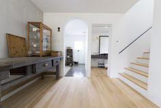 モルタルの土間とLDKの間の仕切りはアーチ型に。アンティークの家具が、自然豊かな郊外での暮らしにしっくりなじむ。