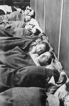 SHELTER PHOTOGRAPHS TAKEN IN LONDON BY BILL BRANDT, NOVEMBER 1940. A row of shelterers lie asleep in a North London air raid shelter. The wall against which they are resting their heads is actually that of the latrines!