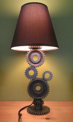 """Simple Gear Industrial Table Lamp The """"Gear Lamp"""" is an Industrial Table Lamp with a Steampunk Design. The lamp is created from used gears that supplied power thru a transmission gearbox. The gears are in their unfinished original condition. Car Part Furniture, Automotive Furniture, Automotive Decor, Furniture Decor, Furniture Design, Rustic Furniture, Vintage Furniture, Furniture Outlet, Vintage Lamps"""