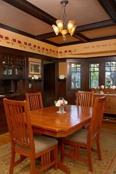 The dining room retains original dark-stained woodwork, now embellished with a painted poppy frieze and vintage lighting.