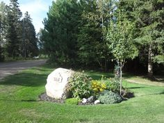 here's the flower bed at the front of the property with the house numbers on the granite rock, beautiful