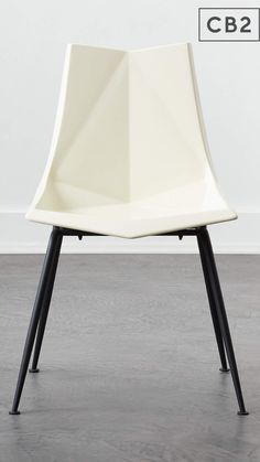 It doesn't get much more midcentury than this classic white dining chair designed by Paul McCobb. Sculptural seat is constructed of molded fiberglass in a matte ivory, supported by matte black powdercoated legs. CB2 exclusive.