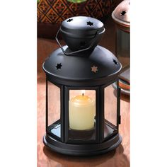 """Quaint colonial styling and a sleek, modern matte black finish make this lamp a winning addition to your decor! Your favorite pillar candle looks lovely at center stage behind six clear glass panels; just the right accent to make any evening into a special occasion. Weight 1 lb. Iron and glass. Candle not included. 5"""" diameter x 9 1/2"""" high."""