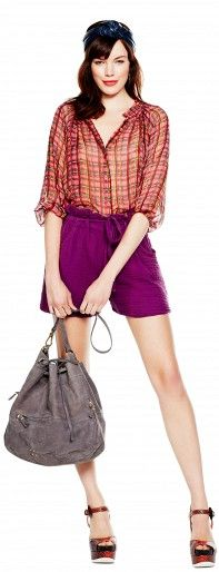 An ethereal sheer blouse and ladylike platforms lend femininity to a pair of paperbag shorts.