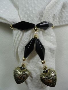 Porta guardanapo confeccionado com contas pretas, douradas e pérola, com corações.