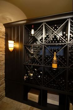 This Wine Cellar is defined by the use of a natural ledge rock wall and a mahogany framed door with a custom iron grill. Plenty of interior space ensures that there will be room for all of your favorite vintages. Photo by Ed Doucet Photography.
