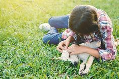 girl playing with little dog Photos Happy girl playing with little dog in nature background, travel on holiday color of vintage tone and by sawitree