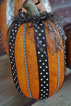 Start with a fake pumpkin, hot glue ribbon in the creases, and top with fringe.