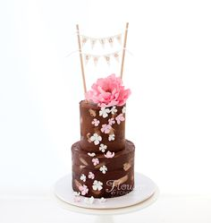 Bridal Shower Cake. Topped with sugar bunting and a pink fantasy flower with a trail of pink & white flowers down the front and brushes of bronze. This semi naked cake was a divine choc mint mud with choc mint ganache layers.