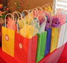 des sachets en papier multicolores contenant des cadeaux d'invités d'anniversaire d'enfant
