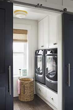 The compact laundry room is super-functional thanks to built-ins surrounding the washer and dryer, and another wall of cabinets with a countertop for folding clothes on the opposite side of the room. Located on the second floor, the room is convenient to all bedrooms; sliding barn doors make it simple to close the room off from view. Built-ins: BOJ Construction Sliding double barn doors: Redi-Prime Shaker-style 8782; Simpson Door Company Paint: Gray Flannel; Olympic Lighting: Schoolhouse ...