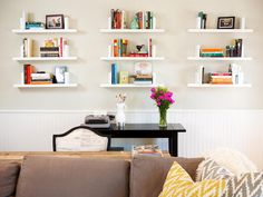 White floating shelves display books and photos in this transitional living room. Hung above white beadboard and a small black desk, the shelves create a functional gallery wall of personal items.