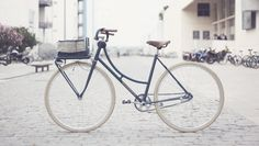 Indigo   Standbikeme Basis: Biciclette Montana Client: Estefanía Frame Style: City Bike Frame Size: 54 Frame Date: 80's Finish: Indigo Colour Coated Speed: Single speed with coaster brake Components: Short brown CINTES leather grip with laces, front rack with handmade cotton basket, Brooks flyer S aged saddle, coaster brake, Wellgo pedals and Schwalbe tires delta cruiser cream, restored crank-set, stem and seat post.