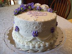 Almond Sour Cream Cake - Almond sour cream cake I made for a friend's birthday. I had left over purple flowers from the last wedding cake that I made, so I used those. They are made from royal icing mixed in with some gum paste leaves along with butter cream leaves. Decorations on the side are butter cream icing. Thanks for looking.