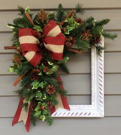 HOW ABOUT UNIQUE, GORGEOUS, RUSTIC, ELEGANT ALL IN ONE?! This frame has been painted red then white and then lightly sanded so the red shows through. Then loads of gorgeous Christmas greenery added along with pinecones and berries, cinnamon sticks, and rusted snowflakes, and adorned with a beautiful red & natural burlap type bow accented with a rusty bell. A jute hanger is attached. Just unbox it and hang! Measure 24 tall x 22 wide x 6 deep. Would be gorgeous accenting a wall or door or j... Christmas Greenery, Christmas Door Decorations, Christmas Frames, Christmas Porch, Christmas Bows, Diy Christmas Gifts, Holiday Wreaths, Christmas Holidays, Holiday Decor