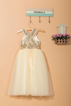 This ankle-length flower girl dress is made by fashionable sequins and soft tulle. With sparkling gold sequins on the bodice and an elegant cross back, the ivory cream dress looks chic and glamourous. The dress is fully lined with satin. The skirt is princess style with five layer of soft tulle which is suitable for girls aging from 1 to 14 years old. This beautiful, elegant and stylish handmade flower girl dress is perfect for wedding, and any special occasions or a simply dressing up item…