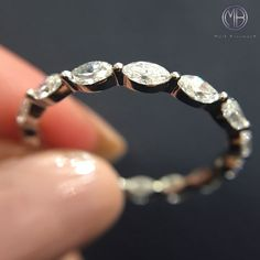 This dainty and beautiful marquise diamond eternity band will look perfect paired with an engagement ring or all by itself.