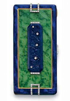 AN ART DECO NEPHRITE, LAPIS LAZULI AND DIAMOND VANITY CASE The rectangular blue enamel case in-set with nephrite and a rectangular raised carved lapis lazuli plaque with collet-set and single-cut diamond accents, the terminals with openwork diamond detail, the diamond pushpiece opening to reveal a fitted mirror, two covered compartments and a lipstick holder, mounted in gold, circa 1930,