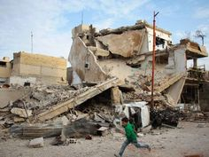 A Syrian boy runs past a destroyed building during