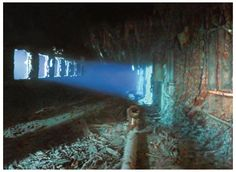 The Promenade  Lights from a submersible penetrate the rusted ruin of Titanic's first-class promenade