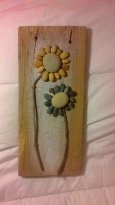 Cuadro hecho con ramas, tabla de madera y piedras
