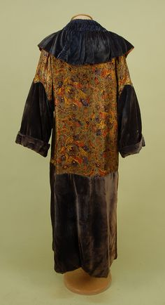 Back View VELVET and METALLIC BROCADE EVENING COAT, c. 1920. Changeable blue velvet with ruched and ruffled collar, cuffed sleeve, upper body and sleeve top of floral brocade in gold, blue, red and black with silver metallic threads, single brocade button with loop.