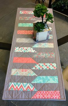 This hand made, reversible, quilted table runner is made with 100% cotton fabric in colors of gray, turquoise, coral and white and measures 16 1/4 x 38 1/4. The top features solid gray and various fabrics in coral, turquoise and white prints. The back is turquoise with small white