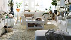 """yes!!!!!!!! Entspannter Komfort; ein Wohnzimmer mit EKTORP 2er-Sofas und EKTORP BROMMA Hocker mit Bezug """"Blekinge"""" in Weiß, HEMNES Couchtisch in Weiß, LINDVED Beistelltisch in Weiß, IVAR Regalkombination aus Kiefer und langflorigen FLOKATI Teppichen in Weiß"""