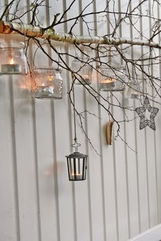 Christmas or anytime idea! Simple Scandinavian design of birch tree branch attached to wall, with lanterns hanging from it.