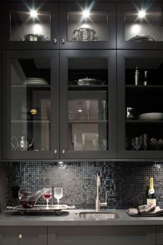 Contemporary butler's pantry. Love the glass mosaic and glass cabinets.