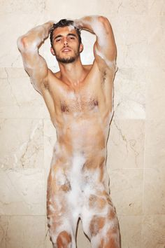 A nude man covered with soapsuds